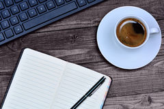 Notebook with keyboard computer and coffee cup on desk. Closeup royalty free stock photos