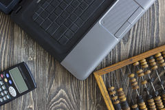 Notebook laptop bills and calculator lying on a wooden table Stock Images