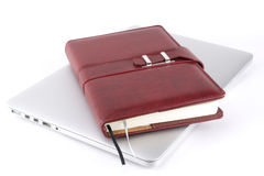 Notebook on a laptop. Brown leather notebook on a laptop. White background Royalty Free Stock Photography