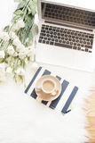 Notebook, laptop, a cup of coffee and a large bouquet white flowers on the floor on a white fur carpet. Freelance fashion comforta Stock Image