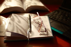 Notebook, laptop, pen, glasses a and books. Royalty Free Stock Photography
