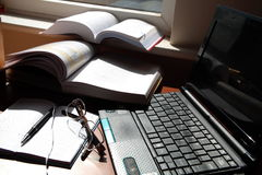 Notebook, laptop, pen, glasses a and books. Stock Photography
