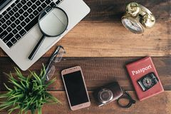 Notebook, laptop, smartphone, compass, passport, clock and camera on wooden table background Royalty Free Stock Photography