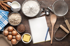 Notebook List Cooking Baking. A blank white notebook with various food ingredients and cooking utensils on a wood background Stock Image