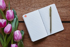 Notebook with little heart tulips in vivid atmosphere Stock Images