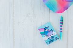 Notebook with llama unicorn and rainbow with colorful gel pen and rainbow cap on white wooden background. Idea of Girly. Desk table. Back to school concept royalty free stock photos