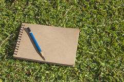 Notebook lying on green grass Stock Image