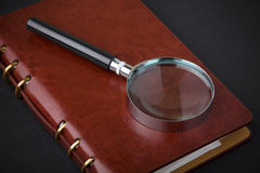 Notebook with a magnifier Stock Photography