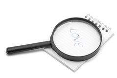 Notebook and magnifier Stock Image