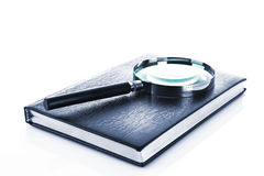 Notebook with a magnifier on it isolated Royalty Free Stock Photos