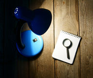 Notebook and magnifier in the light of lantern. Stock Photos