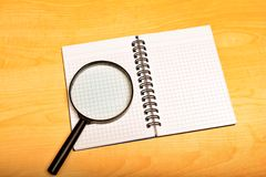 Notebook and magnifier Royalty Free Stock Image