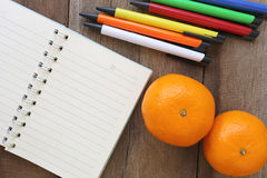 Notebook and mandarin oranges on old wood for the design backgro Stock Images