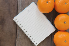 Notebook and Mandarin oranges placed on the old wooden floor. Royalty Free Stock Image