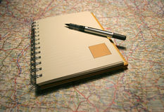 Notebook on a map. Planning your holidays Royalty Free Stock Image