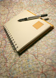 Notebook on a map. Planning your holidays Royalty Free Stock Images