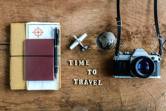 Notebook with map, passport and camera on wooden background Stock Photos