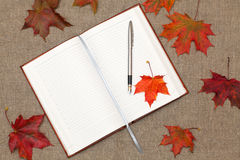 Notebook and maple leaves. Open notebook and maple leaves on the table Stock Images