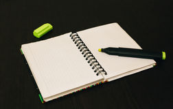 Notebook with a marker on the table, opened on a blank sheet. Workplace, notebook open on a clean white sheet, marker green with an open cap Royalty Free Stock Photography