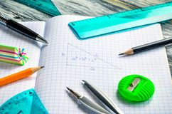 Various school supplies. Notebook and mathematical accessories on a wooden background royalty free stock photography