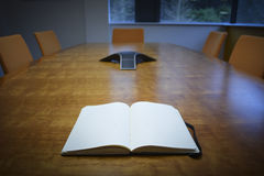 Notebook on Meeting Room Desk. Notebook on Meeting or Board Room Wooden Desk surrounded by empty chairs Royalty Free Stock Photos