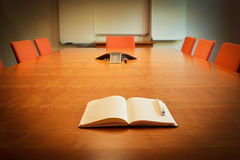 Notebook on Meeting Room Desk. Notebook on Meeting or Board Room Wooden Desk surrounded by empty chairs Royalty Free Stock Photo