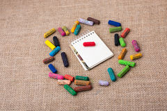Notebook in the middle of crayons Royalty Free Stock Photography