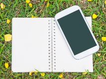 Notebook and mobile phone on green grass Royalty Free Stock Images
