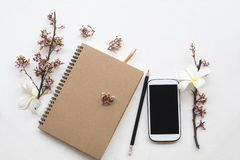 Notebook ,mobile phone of student writing note for study. With pencil ,flower arrangement flat lay style on background white stock images