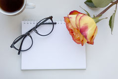 Notebook mock up for artwork with red and yellow rose, gasses and cup of black coffee. Top view. Place for text. Fresh Royalty Free Stock Photos