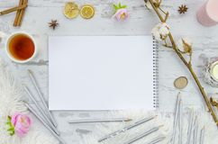 Notebook mock up for artwork with pencils and tea on wooden background. View from above. Artistic work tools. Royalty Free Stock Photos