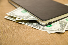 Notebook and money on the old tissue Royalty Free Stock Photo