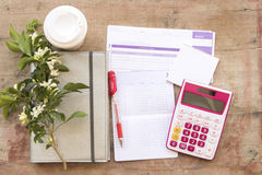 Notebook monthly planner record for financial and check money. Background notebook monthly planner record for financial with coffee cup and flowers royalty free stock photos