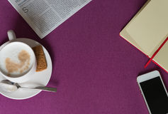 Notebook, morning coffee with milk foam, smartphone and newspape Stock Image