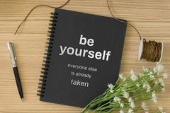 Notebook with wisdom quote and laptop on wood background. stock photos