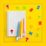 Notebook with with multicolored numerals, calculator and hand spinner - antistress. On yellow background. Overhead food shots. Copy-space composition. Back to Royalty Free Stock Image