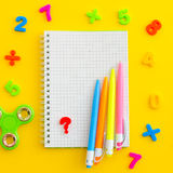 Notebook with multicolored numerals, pens and hand spinner - antistress. On yellow background. Overhead shots. Copy-space composition. Back to school concept Stock Photography