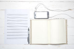 Notebook with music paper note and smart phone Stock Photography