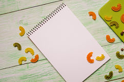 Notebook with noodles on wooden Royalty Free Stock Photography