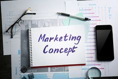 Notebook with. `MARKETING CONCEPT` words and stationery on office table Royalty Free Stock Image