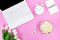 Notebook Notepad Alarm Clock Bouquet of tulips Popcorn in a bowl on the desktop stock photo