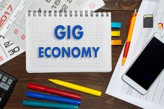 Notebook with a notes gig economy on the office table with tools.  royalty free stock images