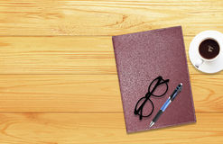 Notebook with office supplies with pen with glasses and cup of c Stock Images