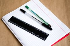 Notebook. Office to work in the office. School supplies. Pens, pencils, a ruler, a clean notebook. White list. Working environment. Preparation for work stock photo