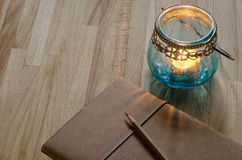 Notebook with an old candle lantern Stock Photos
