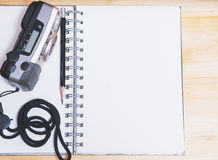 Notebook with old film compact camera and black pencil. Stock Photo