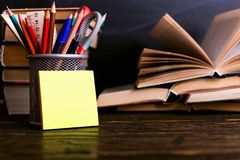 Notebook, open books and stand for pens on a dark wooden table on the background of chalk board. Learning knowledge at school,. Notebook, open books and stand stock photo