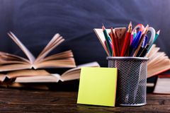 Notebook, open books and stand for pens on a dark wooden table on the background of chalk board. Learning knowledge at school, stock photo