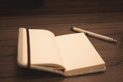 Notebook open with pen on wooden table; business and study object. Royalty Free Stock Photos