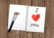 Notebook opened on old vintage wooden table with I love you handwritten and red heart shape painted with makeup paintbrush as stock photo